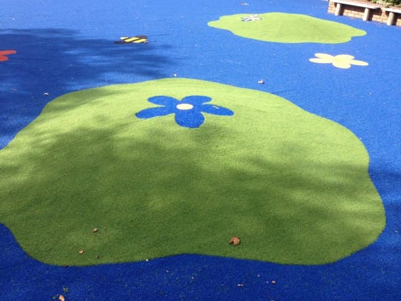 blue and green nursery area with green artificial hills and flower design
