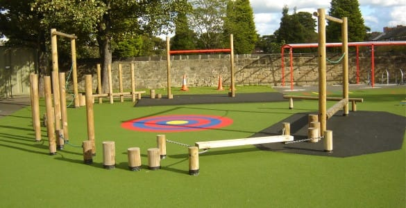 trim trail installation with wooden playground equipment and a red and blue target