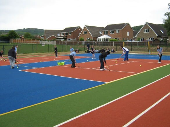 pupils playing hockey on new multi use games area