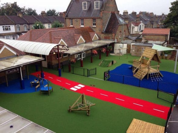 playground surface with play equipment, a red roadway and landscaping area