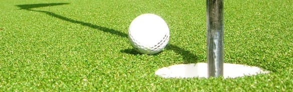 golf ball going into cup on artificial grass putting green
