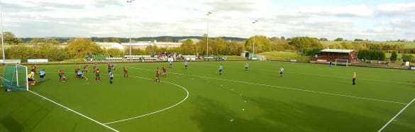 users playing hockey on a full green artificial grass hockey pitch