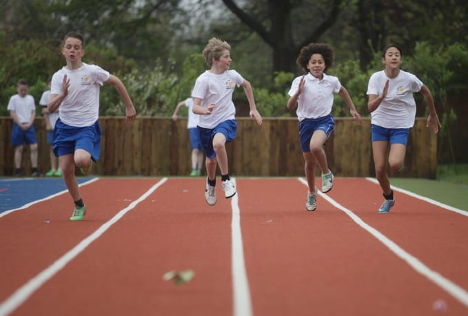 four children racing on running track