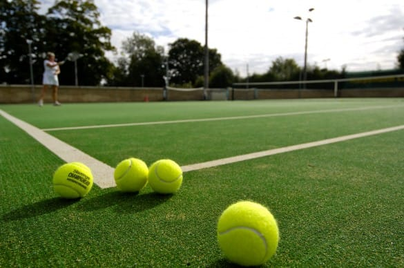 four tennis balls placed on artificial grass tennis court