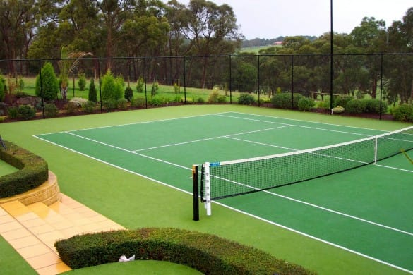 view of two colour green synthetic tennis court with white markings and net