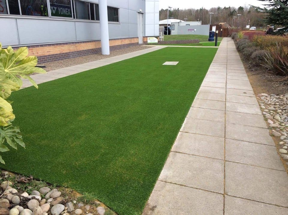 strip of artificial grass being maintained outside business