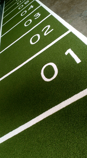 green and white artificial grass performance track with numbers