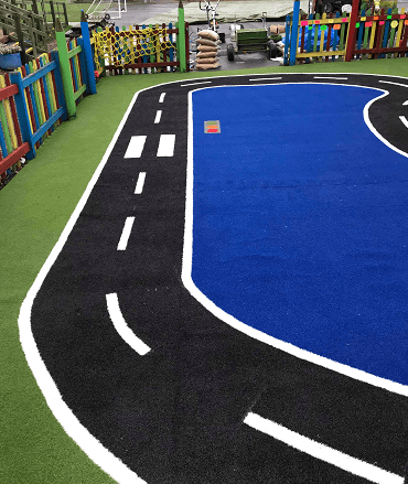 astro turf playground with road
