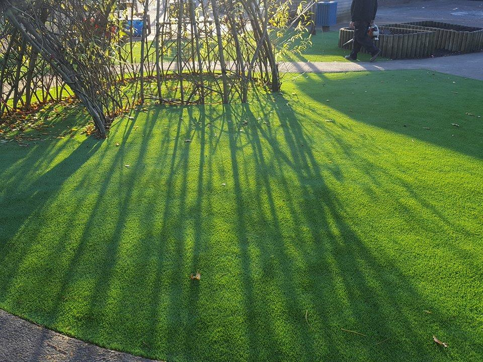 close up of artificial grass landscaping around a tree