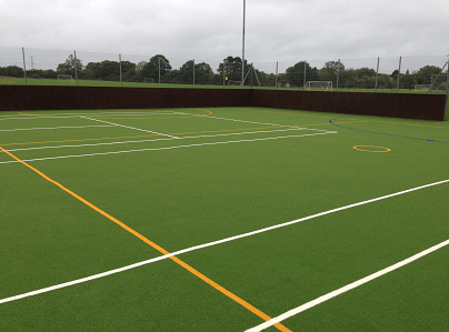 green multi use games area with yellow and white line markings