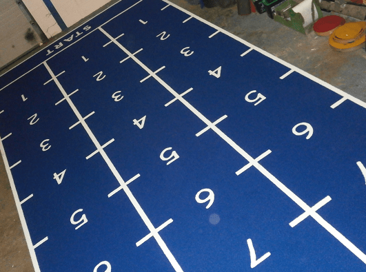 blue sled track gym flooring showing numbers in white cut in