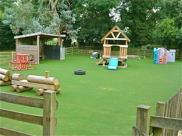 children's play area with play equipment and synthetic grass surfacing