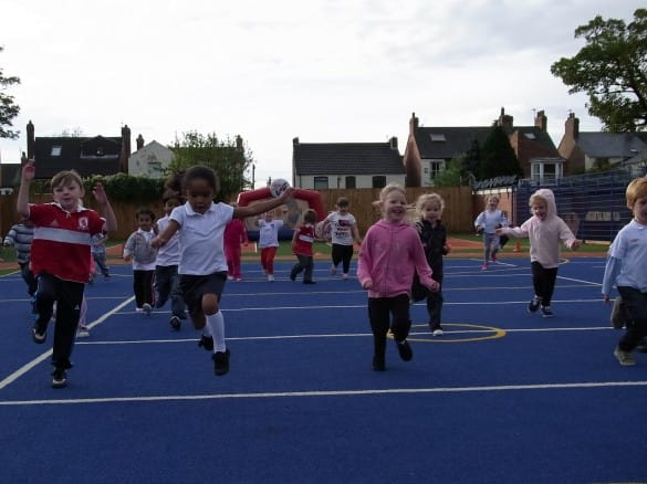 primary school pupils playing on blue muga