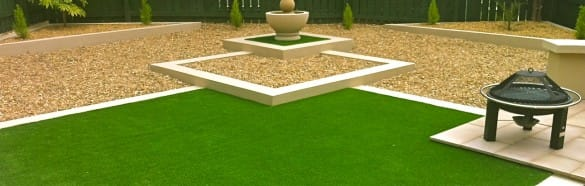 landscape garden with gravel, fire pit and sculpture around artificial turf