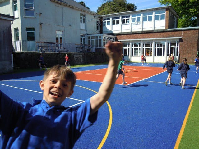 primary school pupil looking pleased with new school muga