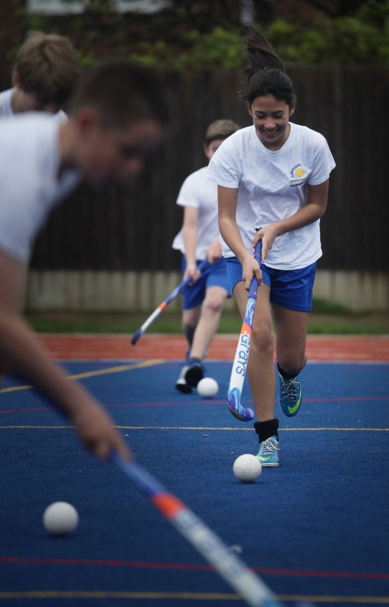 pupils playing hockey on synthetic turf muga