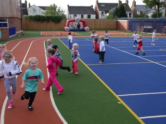 young children playing on school muga