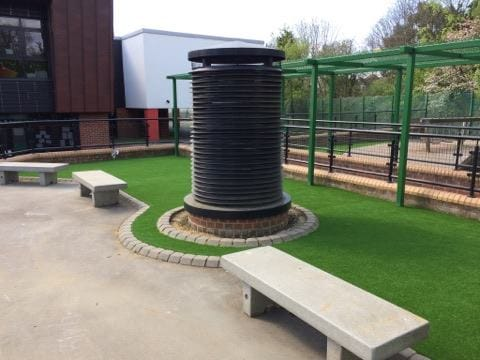 school seating area in front of artificial grass green area