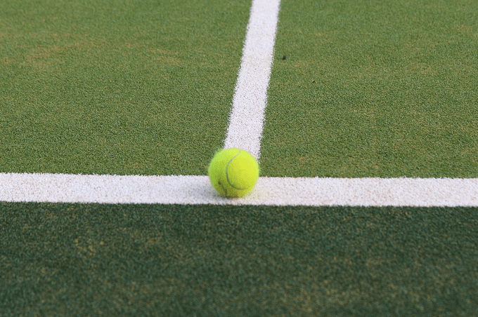 tennis ball on artificial turf tennis court in white and green